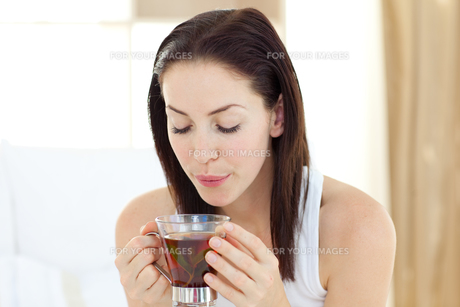 Delighted woman drinking teaの素材 [FYI00482467]