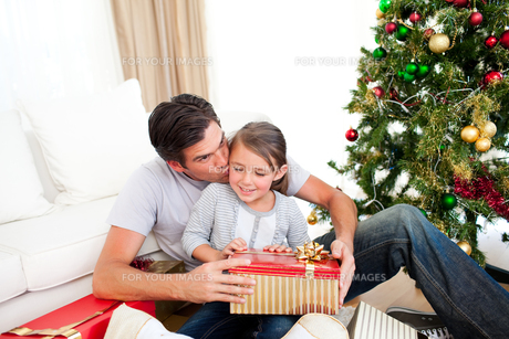 Father kissing his little daughter after giving her a Christmas giftの写真素材 [FYI00482470]