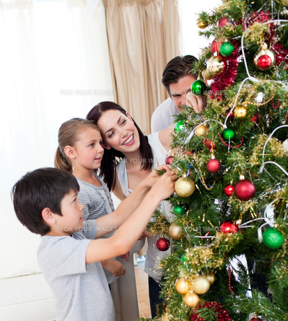 Happy family decorating a Christmas tree with boublesの写真素材 [FYI00482473]
