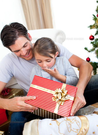 Surprised little daughter opening a Christmas present with her fatherの素材 [FYI00482475]
