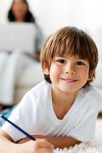 Smiling little boy drawing lying on the floorの写真素材 [FYI00482481]