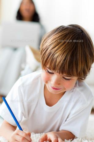 Adorable little boy drawing lying on the floorの写真素材 [FYI00482482]