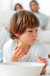 Little boy eating chips lying on the floorの写真素材 [FYI00482483]