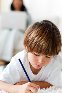 Concentrated little boy drawing lying on the floorの写真素材 [FYI00482484]