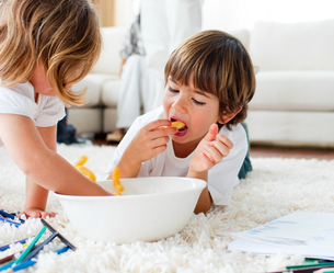Cute children eating chips and drawingの写真素材 [FYI00482486]