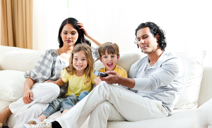 Excited little boy watching TV with his familyの写真素材 [FYI00482487]