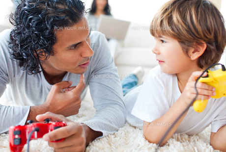 Father and his little boy playing video games lying on the floorの写真素材 [FYI00482494]