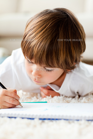 Serious little boy drawing lying on the floorの写真素材 [FYI00482577]