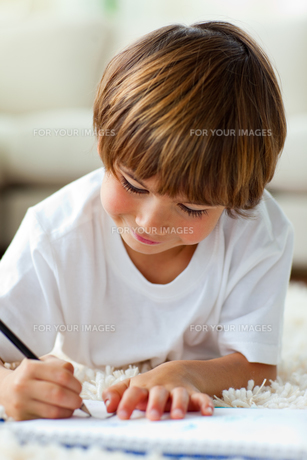 Jolly little boy drawing lying on the floorの写真素材 [FYI00482578]
