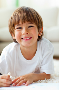 Happy little boy drawing lying on the floorの写真素材 [FYI00482579]