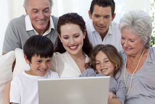 Family sitting on sofa using a laptopの写真素材 [FYI00482586]