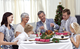 Family eating turkey in Christmas Eveの写真素材 [FYI00482587]