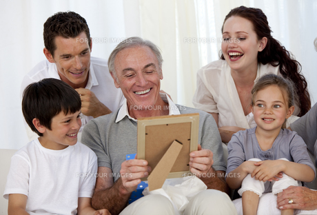 Grandfather looking at a photo with his familyの写真素材 [FYI00482588]