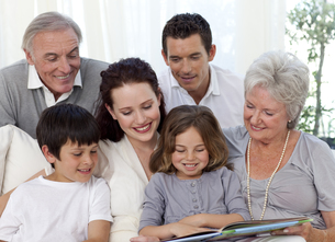 Family sitting on sofa reading a bookの写真素材 [FYI00482589]