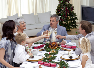Family tusting in a Christmas dinner with champagneの素材 [FYI00482591]