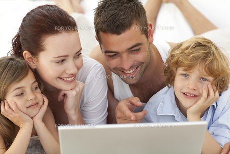 Portrait of family in bed using a laptopの写真素材 [FYI00482593]
