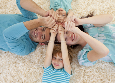 Happy family on floor with heads and hands togetherの写真素材 [FYI00482596]