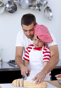 Father helping his son cutting breadの写真素材 [FYI00482598]