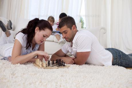 Couple playing chess on floor in livingroomの写真素材 [FYI00482608]