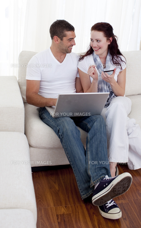 Couple buying online with a credit card on sofaの写真素材 [FYI00482610]