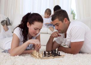 Parents playing chess on floor in livingroomの写真素材 [FYI00482611]