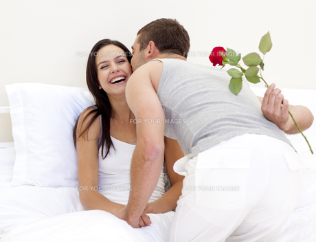 Man giving a rose and a kiss to his beautiful wifeの写真素材 [FYI00482617]