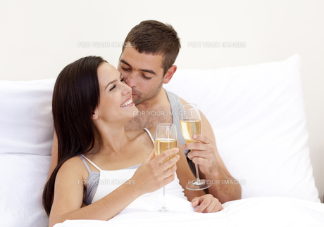 Lovers drinking champagne in bedの写真素材 [FYI00482620]