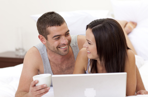Husband and wife in bed using a laptopの写真素材 [FYI00482623]
