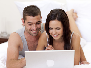 Couple in bed using a laptopの写真素材 [FYI00482624]