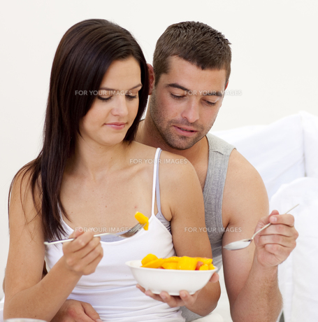 Young couple eating fruit in bedの素材 [FYI00482626]