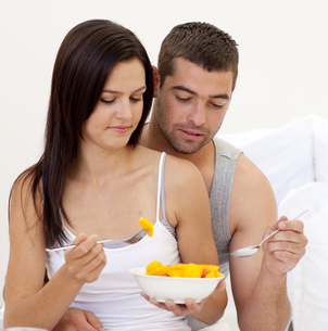 Young couple eating fruit in bedの写真素材 [FYI00482626]