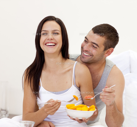 Smiling couple having nutritive breakfast in bedの写真素材 [FYI00482628]