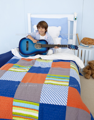 Little boy playing guitar in bedroomの素材 [FYI00482629]