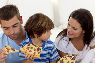Prents and son eating pizza in livingroomの写真素材 [FYI00482631]