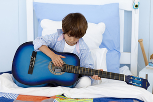 Little boy playing guitar in bedの写真素材 [FYI00482632]
