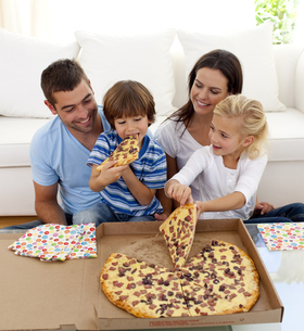 Young family eating pizza in livingroomの写真素材 [FYI00482634]