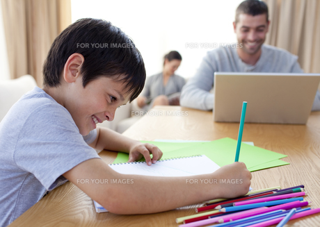 Boy drawing and parents working at homeの写真素材 [FYI00482639]
