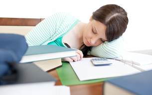 Young tired woman studying on a tableの写真素材 [FYI00482646]
