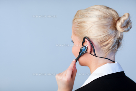 Woman talking on a headset with focus on headsetの写真素材 [FYI00482660]