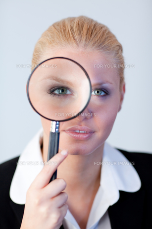 Serious Business woman looking through a magnifying Glassの写真素材 [FYI00482663]