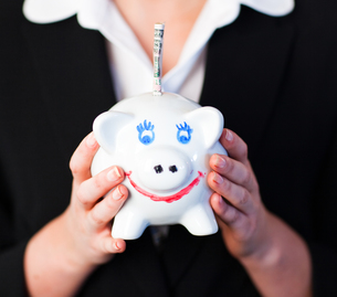 Woman Holding a piggy bank with dollars in itの写真素材 [FYI00482668]