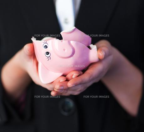 Business woman holding a broken piggy bankの写真素材 [FYI00482669]