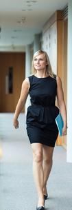 Confident businesswoman walking through a corridorの写真素材 [FYI00482676]