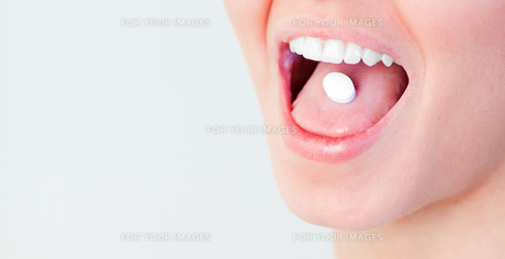 Woman with a pill in her mouthの素材 [FYI00482728]