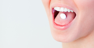 Woman with a pill in her mouthの写真素材 [FYI00482728]