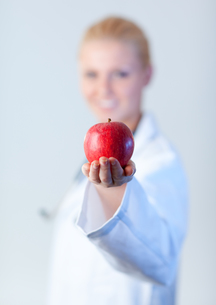 Doctor holding an apple with focus on the appleの素材 [FYI00482729]