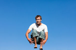 Handsome man jumping against a blue backgroundの素材 [FYI00482740]