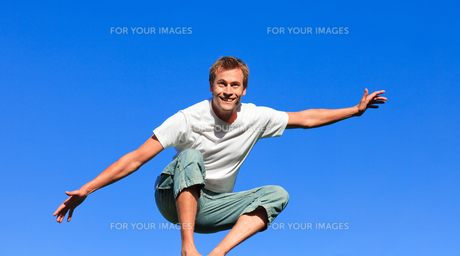 Nice man jumping against a blue backgroundの写真素材 [FYI00482741]