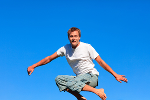 Selfassured man jumping against a blue backgroundの写真素材 [FYI00482742]