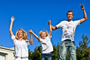 Smiling family jumping against a blue backgroundの写真素材 [FYI00482743]
